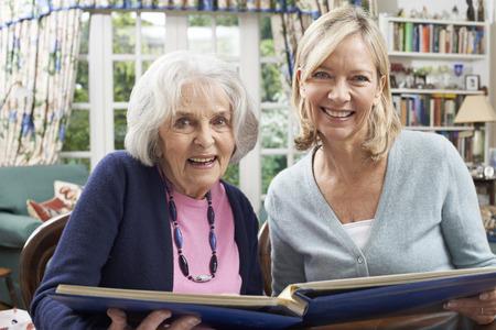 neighbor: Senior Woman Looks At Photo Album With Mature Female Neighbor Stock Photo