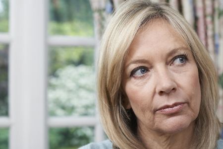Head And Shoulders Portrait Of Unhappy Mature Woman At Home Standard-Bild