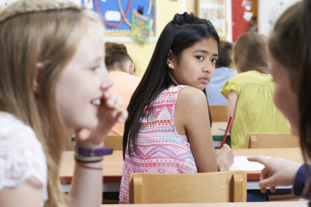 教室で学校の友達にうわさされている不幸な少女 写真素材