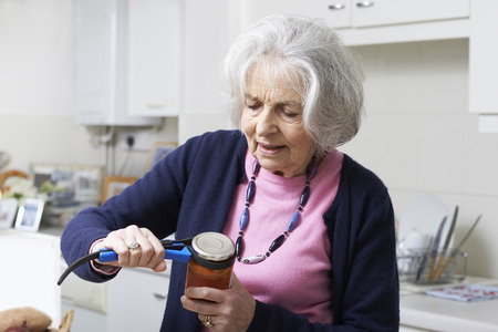 年配の女性が台所援助が付いている瓶の蓋の離陸 写真素材