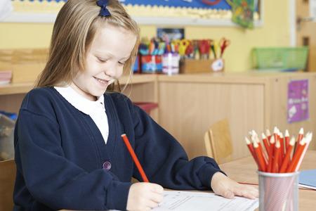 school desk: Female Elementary School Pupil Working At Desk