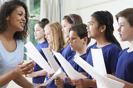 Group Of School Children With Teacher Singing In Choir Stock Photo