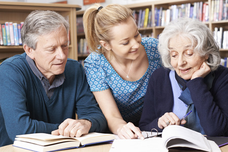 the elderly tutor: Mature Students Working With Teacher In Library Stock Photo