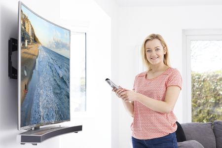 flat screen: Young Woman With New Curved Screen Television At Home Stock Photo