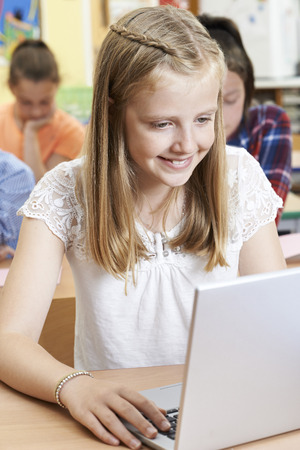 Female Elementary School Pupil Using Laptop In Computer Class Stock Photo