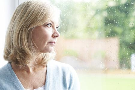 soledad: Triste mujer madura que sufre de agorafobia mirando por la ventana