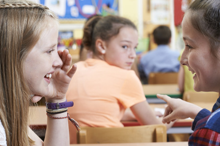 peer pressure: Unhappy Girl Being Gossiped About By School Friends In Classroom
