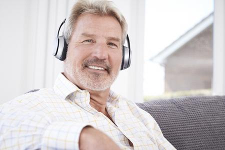 mature man: Mature Man Listening To Music On Wireless Headphones
