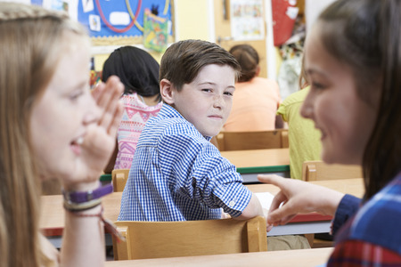 peer pressure: Unhappy Boy Being Gossiped About By School Friends In Classroom