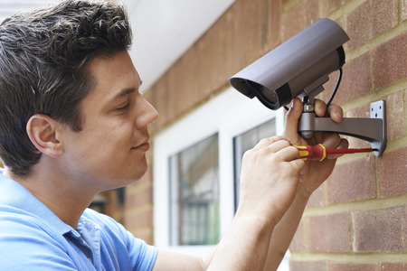 fitting: Security Consultant Fitting Security Camera To House Wall