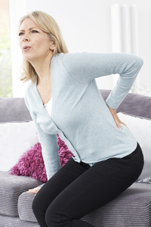 Mature Woman Suffering From Backache At Home Stock fotó
