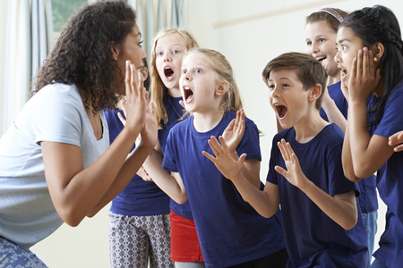 Group Of Children With Teacher Enjoying Drama Class Together Фото со стока