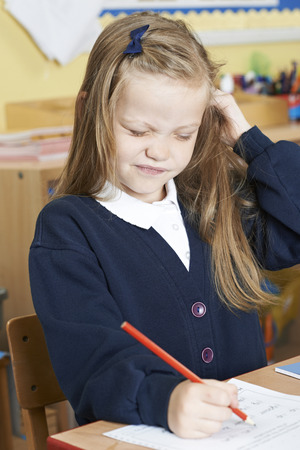 lice: Female Elementary Pupil Suffering From Head Lice In Classroom