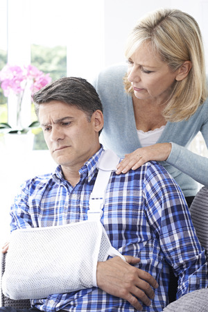 fracture arm: Wife Comforting Husband Suffering With Arm Injury