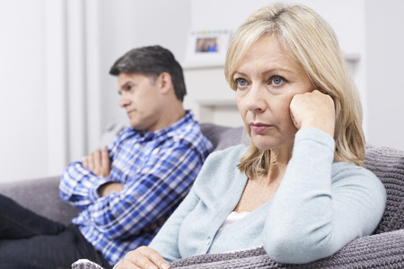 relationship difficulties: Mature Couple With Relationship Difficulties Sitting On Sofa