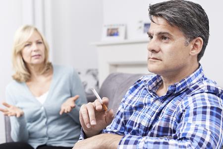 social conflicts: Pareja madura que discuten sobre fumar en el hogar