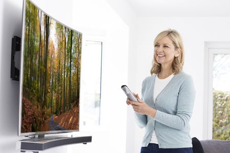 screen: Mature Woman With New Curved Screen Television At Home