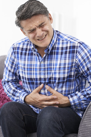 irritable bowel syndrome: Mature Man Suffering From Stomach Pain At Home