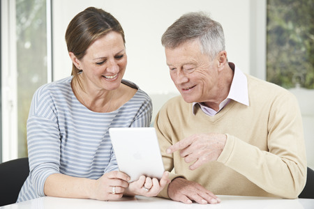 home grown: Senior Man And Adult Daughter Looking At Digital Tablet Together