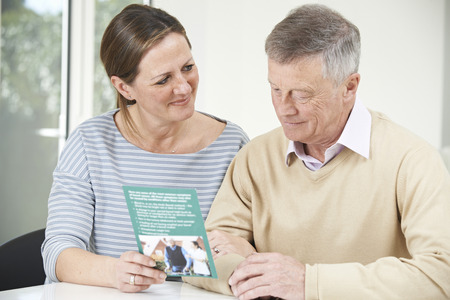 senior adult man: Senior Man With Adult Daughter Looking At Brochure For Retirement Home