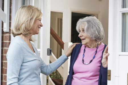 Woman Checking On Elderly Female Neighbor