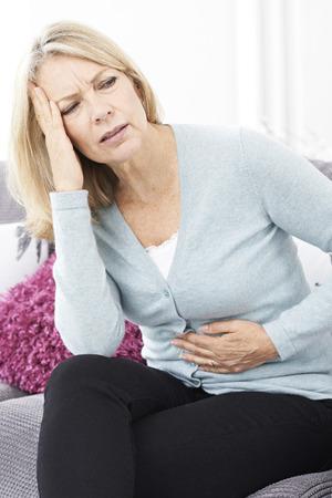 Mujer madura que sufre de dolor de estómago y dolor de cabeza Foto de archivo