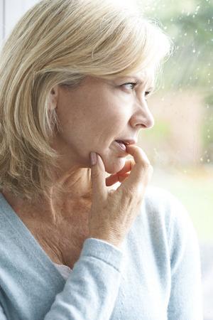 Droevige rijpe vrouw die lijdt aan agorafobie die uit venster kijkt