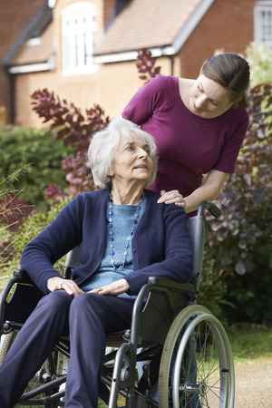 the ageing process: Daughter Pushing Senior Mother In Wheelchair
