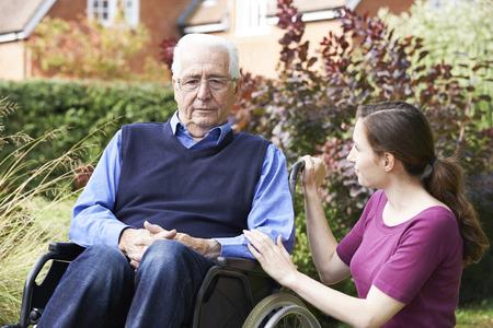 paraplegico: Adult Daughter Comforting Senior Father In Wheelchair Foto de archivo