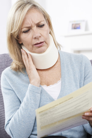 neck injury: Mature Woman Reading Letter After Receiving Neck Injury