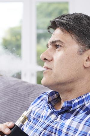 Mature Man Using Vapourizer As Smoking Alternative