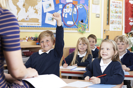 8 years old: Class Of Elementary School Pupils Answering Question Stock Photo