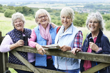 happy senior: Group Of Senior Female Friends Hiking In Countryside