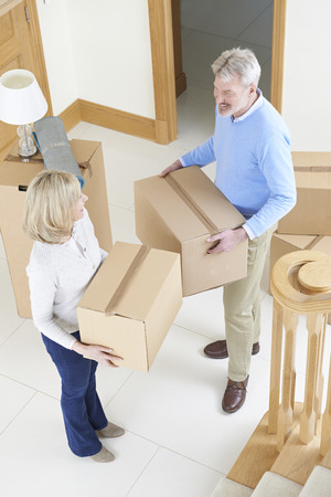 property ladder: Mature Couple Moving In To New Home