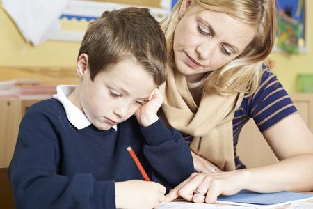 Insegnante Con Maschio scuola elementare Pupilla con il problema