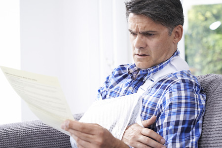 Volwassen man het lezen brief over Injury Stockfoto