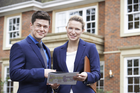 property ladder: Male And Female  Standing Outside Residential Property