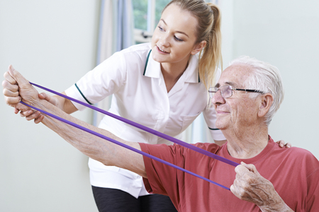 physiotherapist: Senior Male Working With Physiotherapist Stock Photo