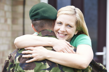 thirties portrait: Portrait Of Wife Hugging Army Husband Home On Leave Stock Photo
