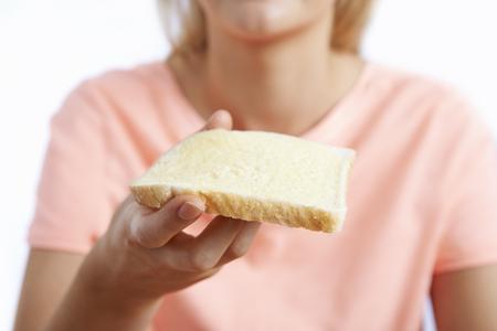 comiendo pan: Mujer que come la rebanada de pan blanco con margarina