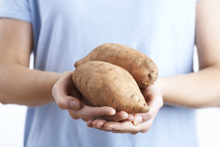 unrecognisable person: Close Up Of Woman Holding Sweet Potato