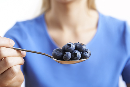 unrecognisable person: Close Up Of Woman With Spoonful Of Blueberries Stock Photo