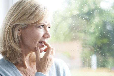 창 밖으로 찾고 광장 공포증에서 고통 슬픈 성숙한 여자 스톡 콘텐츠