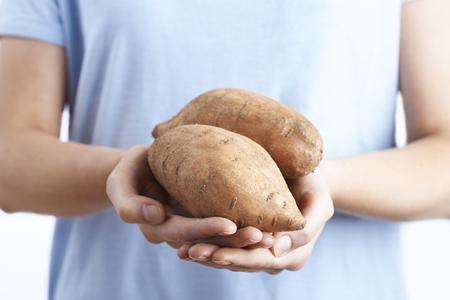 holding close: Close Up Of Woman Holding Sweet Potato