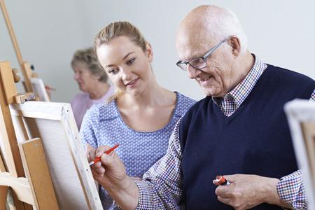 Seniors Attending Painting Class With Teacher Archivio Fotografico
