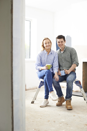 rennovation: Young Couple Sitting In Property Being Renovated