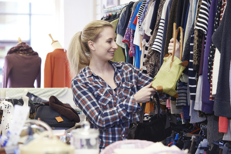 thrift: Female Shopper In Thrift Store Looking At Handbags