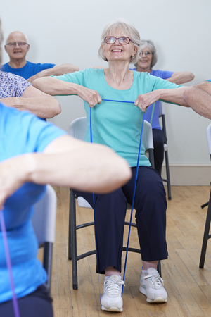 resistance: Group Of Seniors Using Resistance Bands In Fitness Class Stock Photo