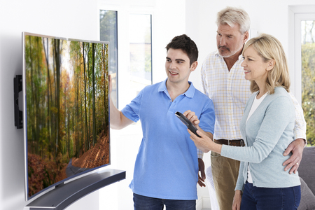hd tv: Man Demonstrating New Television To Mature Couple At Home Stock Photo