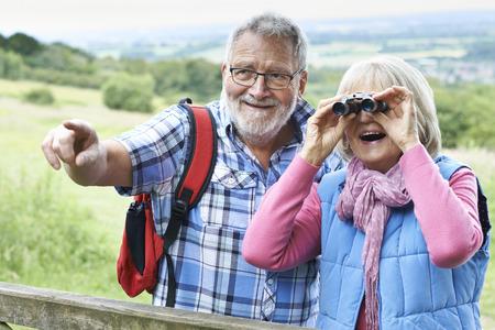 a hobby: Senior Couple Hiking In Countryside Looking Through Binoculars